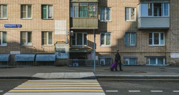 woman in black coat walking on pedestrian lane during daytime